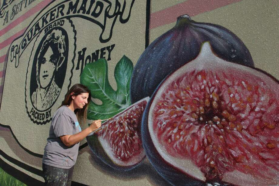 "Friendswood artist Anat Ronen was commissioned to paint a mural showing the town's heritage and culture. The mural includes figs, a staple crop during the community's early years, and a Space Shuttle, symbolilzing how NASA influenced  Friendswood. ""The challenge here was to create something that is both informative but also fun to look at and inviting,"" she says. Photo: Kar B Hlava"