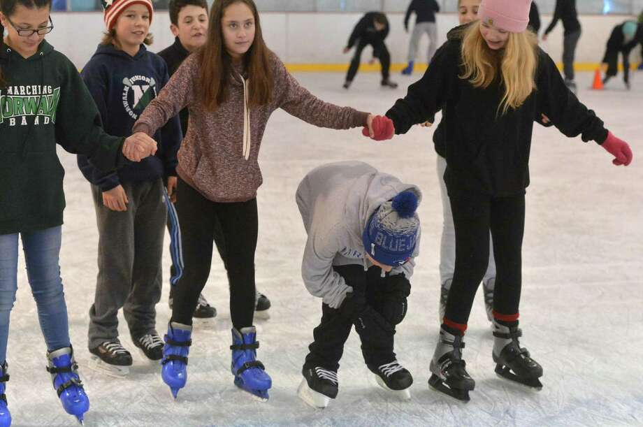 Nathan Hale Middle School seventh-grader Jake Palmer skates under a group of girls arms during a schoolwide skating session at The Rinks at Veterans Park on Monday. Photo: Alex Von Kleydorff / Hearst Connecticut Media / Connecticut Post