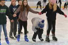 Nathan Hale Middle School seventh-grader Jake Palmer skates under a group of girls arms during a schoolwide skating session at The Rinks at Veterans Park on Monday.