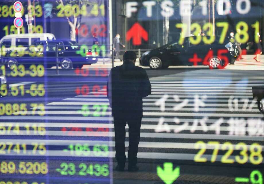 A man is reflected on the electronic board of a securities firm in Tokyo, Monday, Jan. 16 2017. Asian shares were mostly lower Monday morning amid worries about Britain's exit from the European Union, and Takata stock dropped in Tokyo after the air bag maker agreed to a guilty plea in the U.S. over massive recalls. (AP Photo/Koji Sasahara) ORG XMIT: KSX101 Photo: Koji Sasahara / Copyright 2017 The Associated Press. All rights reserved.