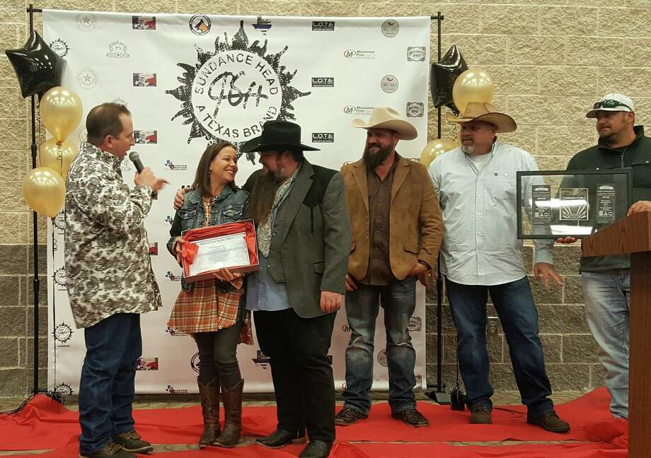 Misty and Sundance Head are surprised with the deed for a binary star system that has been registered in their names during the Sundance Head Appreciation Dinner at Texan Drive Stadium in Porter on Saturday, Dec. 7. From left to right: Allen Rhoden, Misty Head, Sundance Head, Matt Peterson, Scott Baker, Josh Ware. Photo: Melanie Feuk