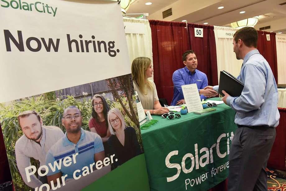 Representatives from SolarCity Seana Meehan, left, and Nick Matthews finish talking to job seeker Michael Kelly of Rensselaer during the Times Union Job Fair at the Albany Marriott hotel on Monday Jan. 16, 2017 in Colonie, N.Y. (Lori Van Buren / Times Union) Photo: Lori Van Buren / 20039450A