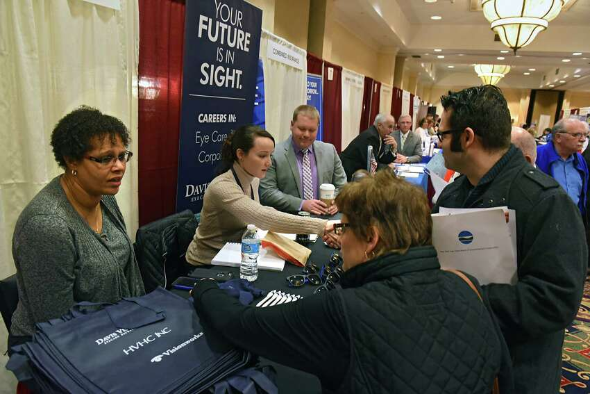 Job seekers talk to representatives at the Davis Vision Insurance Specialist booth during the Times Union Job Fair at the Albany Marriott hotel on Monday Jan. 16, 2017 in Colonie, N.Y. (Lori Van Buren / Times Union)
