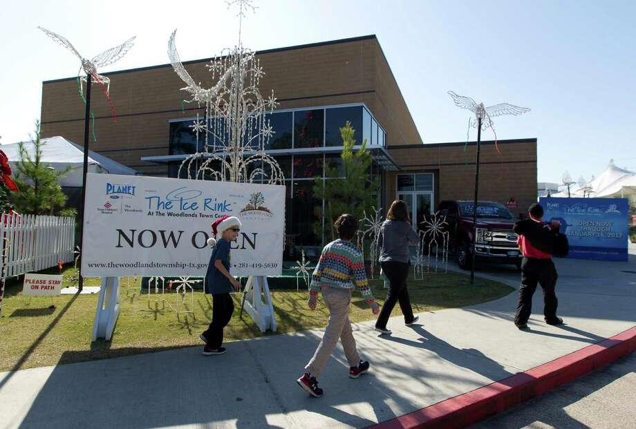 Visitors walk toward The Ice Rink at The Woodlands Town Center in its new location at The Cynthia Woods Mitchell Pavilion Thursday, Dec. 22, 2016, in The Woodlands. The new ice rink facility, which was previously housed for the past 15 years in a tent assembled on the corner of Lake Robbins Drive and Six Pines Drive, was a joint project between The Woodlands Township and the Pavilion. The two entities split the $5.5 million cost to build the 21,000-square-foot building on the Pavilion's property, off of Lake Robbins Drive, and share use of it. The Pavilion uses it as the House of Blues during the summer, while the township transforms it into an ice rink in the winter. Photo: Jason Fochtman, Staff Photographer / Houston Chronicle