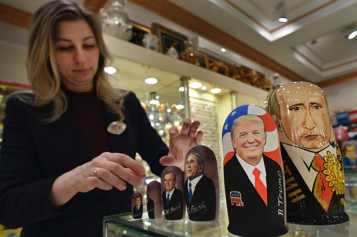 An employee displays traditional Russian wooden nesting dolls, Matryoshka dolls, depicting US President-elect Donald Trump, Russian President Vladimir Putin and other political leaders at a gift shop in central Moscow on January 16, 2017, four days ahead of Trump's inauguration. / AFP / Alexander NEMENOV (Photo credit should read ALEXANDER NEMENOV/AFP/Getty Images)