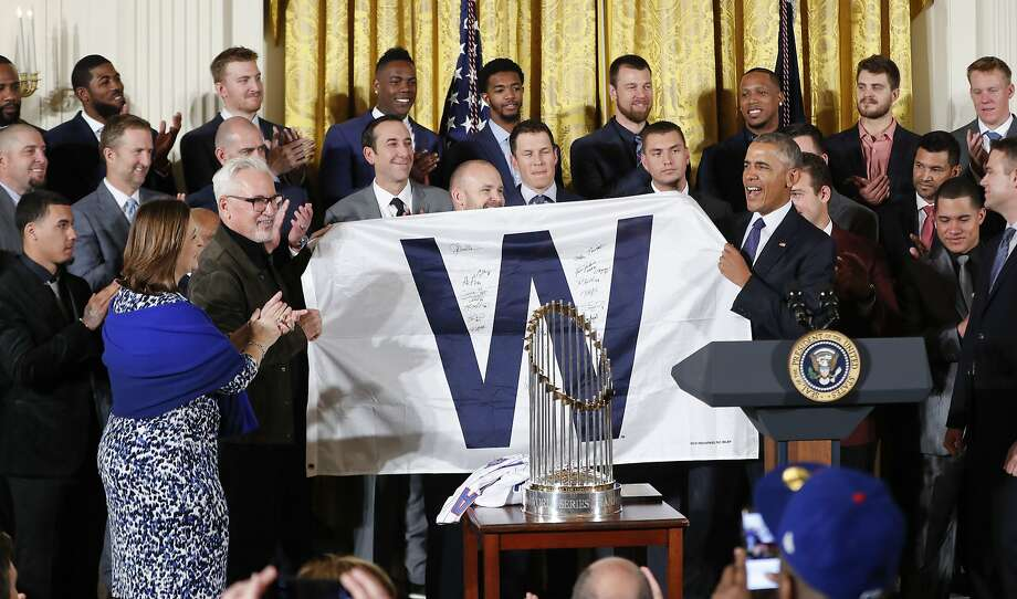 "President Barack Obama holds up a ""W"" flag signed by the Cubs during a ceremony in the East Room of the White House. Photo: Pablo Martinez Monsivais, Associated Press"