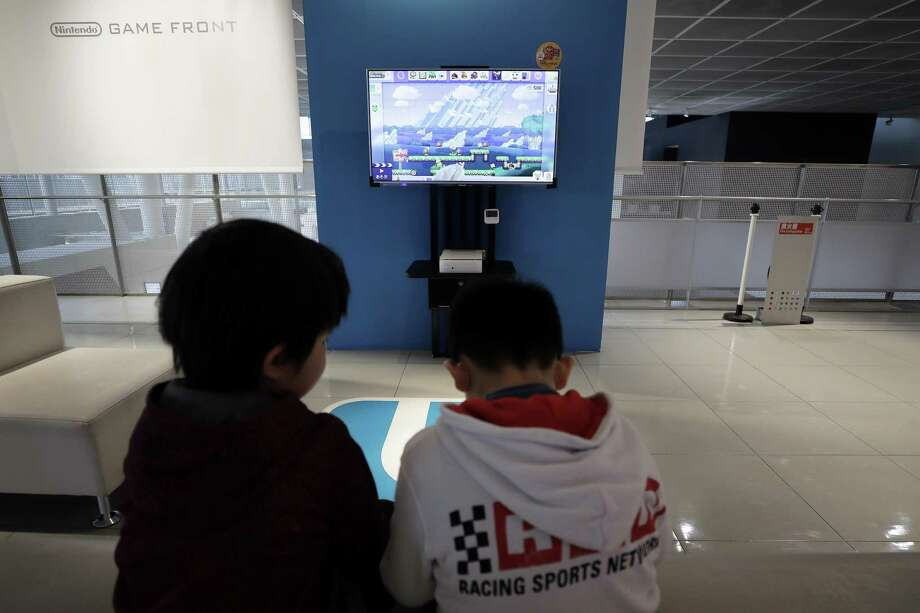 Children play Nintendo Co.'s Super Mario Maker video game using the company's Wii U game console controllers at the Nintendo Game Front showroom in Tokyo, Japan, in December. Parents struggle with enabling excessive video gaming in their children. Photo: Kiyoshi Ota /Bloomberg / © 2016 Bloomberg Finance LP
