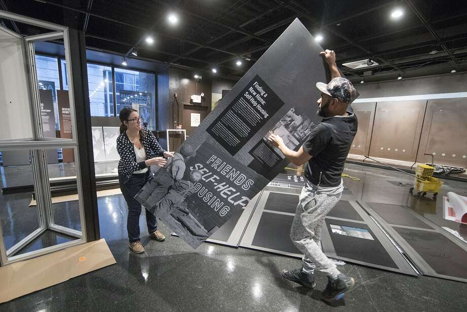 "Elizabeth Tinker and Noah Smalls install the ""Waging Peace"" exhibit at the African American Museum in Philadelphia. Photo: Matt Rourke, Associated Press"