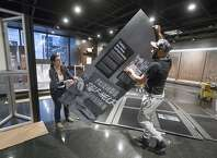 """Elizabeth Tinker and Noah Smalls instal an exhibit at the African American Museum in Philadelphia, Tuesday, Jan. 10, 2017. The American Friends Service Committee is celebrating 100 years of activism with an exhibit called """"Waging Peace. """" (AP Photo/Matt Rourke)"""