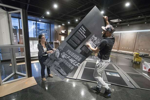 "Elizabeth Tinker and Noah Smalls instal an exhibit at the African American Museum in Philadelphia, Tuesday, Jan. 10, 2017. The American Friends Service Committee is celebrating 100 years of activism with an exhibit called ""Waging Peace. "" (AP Photo/Matt Rourke)"
