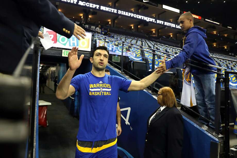 Nicholas Medrios, 12 of Vallejo slaps hands with Golden State Warriors' Zaza Pachulia before Warriors play Cleveland Cavaliers during NBA game at Oracle Arena in Oakland, Calif., on Monday, January 16, 2017. Photo: Scott Strazzante, The Chronicle