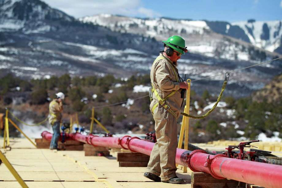 A worker in 2013 helps monitor water pumping pressure and temperatures at the site of a natural gas hydraulic fracturing and extraction operation run by Encana Oil & Gas USA outside Rifle, in western Colorado.  Photo: Brennan Linsley, STF / AP