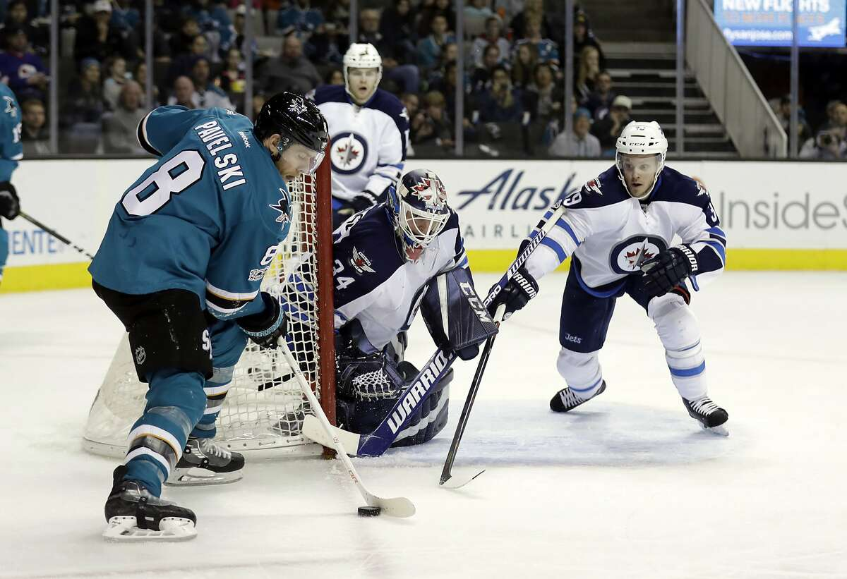 San Jose Sharks' Joe Pavelski (8) controls the puck in front of Winnipeg Jets goalie Michael Hutchinson (34) and Toby Enstrom, right, during the second period of an NHL hockey game, Monday, Jan. 16, 2017, in San Jose, Calif. (AP Photo/Marcio Jose Sanchez)
