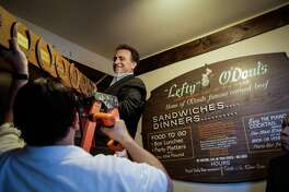Owner Nick Bovis takes down memorabilia from the exterior of his restaurant to move to its new location, after speaking at a press conference regarding the closing of his restaurant Lefty O'Doul's in San Francisco, Calif., on Monday, Jan. 16, 2017.