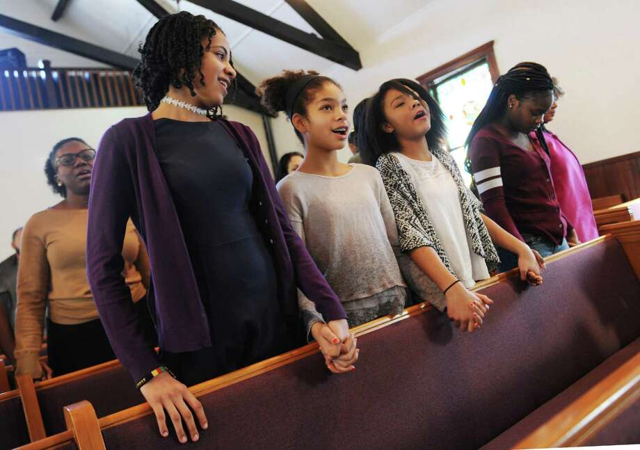 "From left, contest participants eighth-grader Nalani Zhuta-Medley, sixth-grader Aaliyah Brown, seventh-grader Natalie Henry, and eighth-grader Ashanti Headley hold hands while singing ""We Shall Overcome"" during the annual Martin Luther King Oratorical Contest at First Baptist Church in Greenwich. Photo: Tyler Sizemore / Hearst Connecticut Media / Greenwich Time"