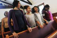 "From left, contest participants eighth-grader Nalani Zhuta-Medley, sixth-grader Aaliyah Brown, seventh-grader Natalie Henry, and eighth-grader Ashanti Headley hold hands while singing ""We Shall Overcome"" during the annual Martin Luther King Oratorical Contest at First Baptist Church in Greenwich."