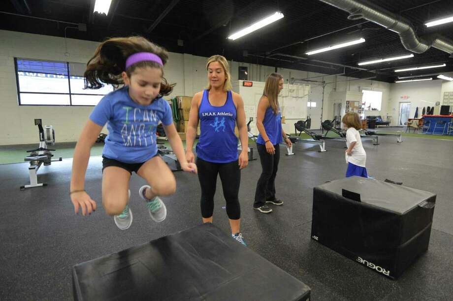 S.M.A.K Co Founder Jenn Fittipaldi watches as her daughter Julia  does some box jumps as kids in the 'Specialized Movement Active Kids' program would do at Crossfit Norwalk. The program for special needs kids helps language and speech development during the exercise program, on Monday january 16, 2017 in Norwalk Conn. Photo: Alex Von Kleydorff / Hearst Connecticut Media / Connecticut Post