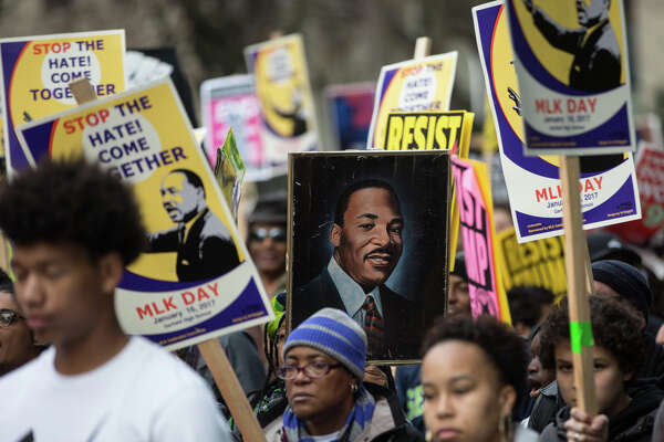 A sign of Martin Luther King Jr. is carried through the crowds during the annual march in celebration of the civil rights leader, on Monday, Jan. 16, 2017.