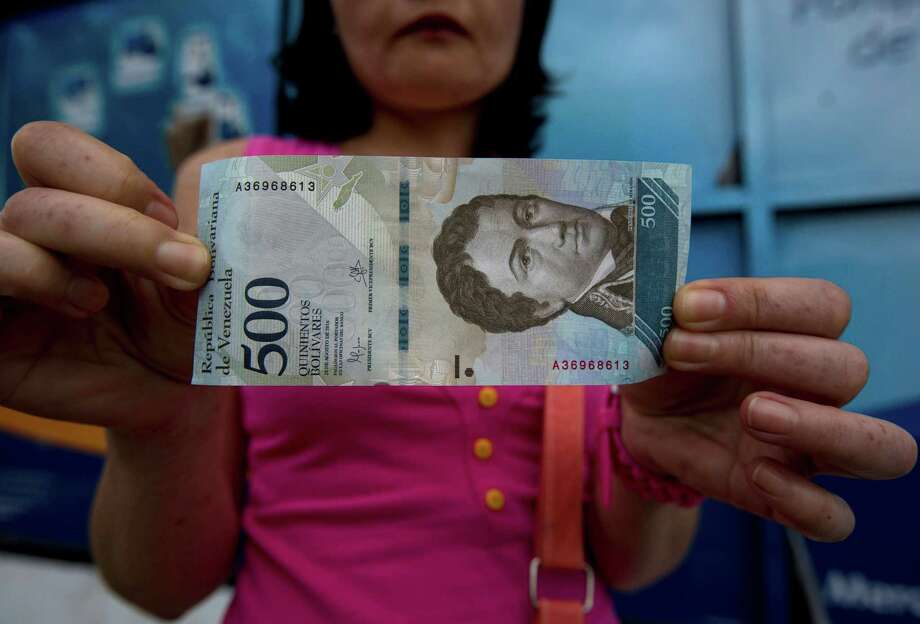 A bank customer in Caracas shows a new 500-bolivar note. Venezuela has replaced the 100-bolivar note with bills ranging from 500 to 20,000 bolivars. Photo: Fernando Llano, STF / Copyright 2017 The Associated Press. All rights reserved.