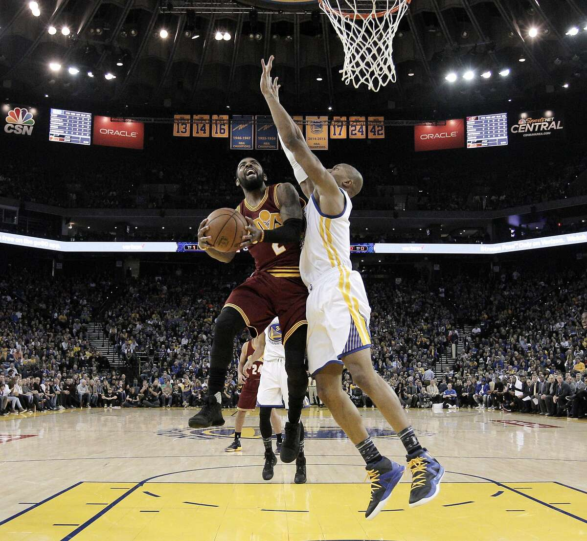 Kyrie Irving (2) drives to the basket defended by David West (3) in the first half as the Golden State Warriors played the Cleveland Cavaliers at Oracle Arena in Oakland, Calif., on Monday, January 16, 2017.