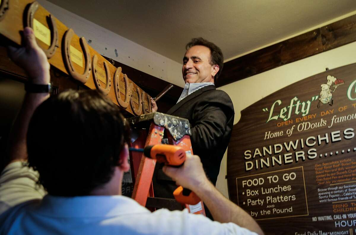 Owner Nick Bovis takes down a plaque from the exterior of his restaurant to move to its new location, after speaking at a press conference regarding the closing of his restaurant Lefty O'Doul's in San Francisco, Calif., on Monday, Jan. 16, 2017.
