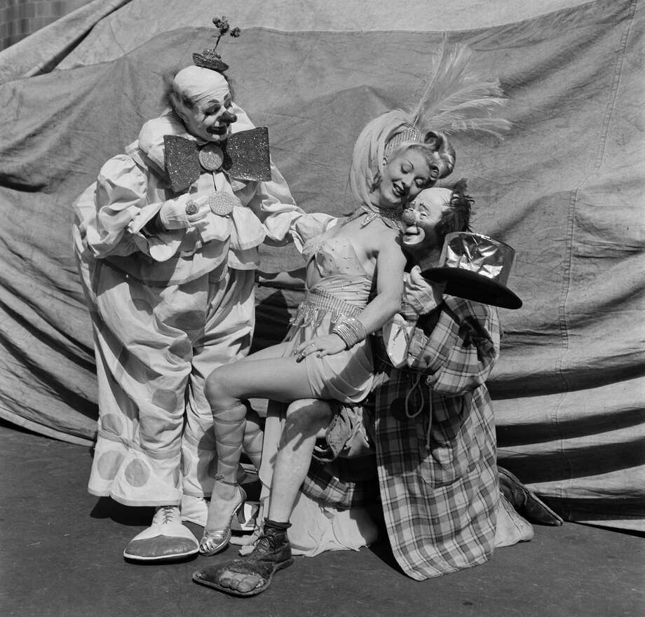 Two clowns and a showgirl pose outside the tent during Ringling Bros. and Barnum & Bailey Circus in New York, New York. (Photo by Earl Leaf/Michael Ochs Archives/Getty Images) Photo: Michael Ochs Archives/Getty Images