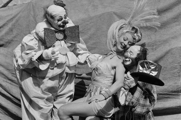 Two clowns and a showgirl pose outside the tent during Ringling Bros. and Barnum & Bailey Circus in New York, New York. (Photo by Earl Leaf/Michael Ochs Archives/Getty Images)