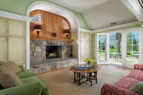 The family room of this presidentially connected house has a vaulted ceiling, stone fireplace flanked by built-in cabinets with hand-painted doors, and an archway topped with a keystone. One wall has a door to the patio.