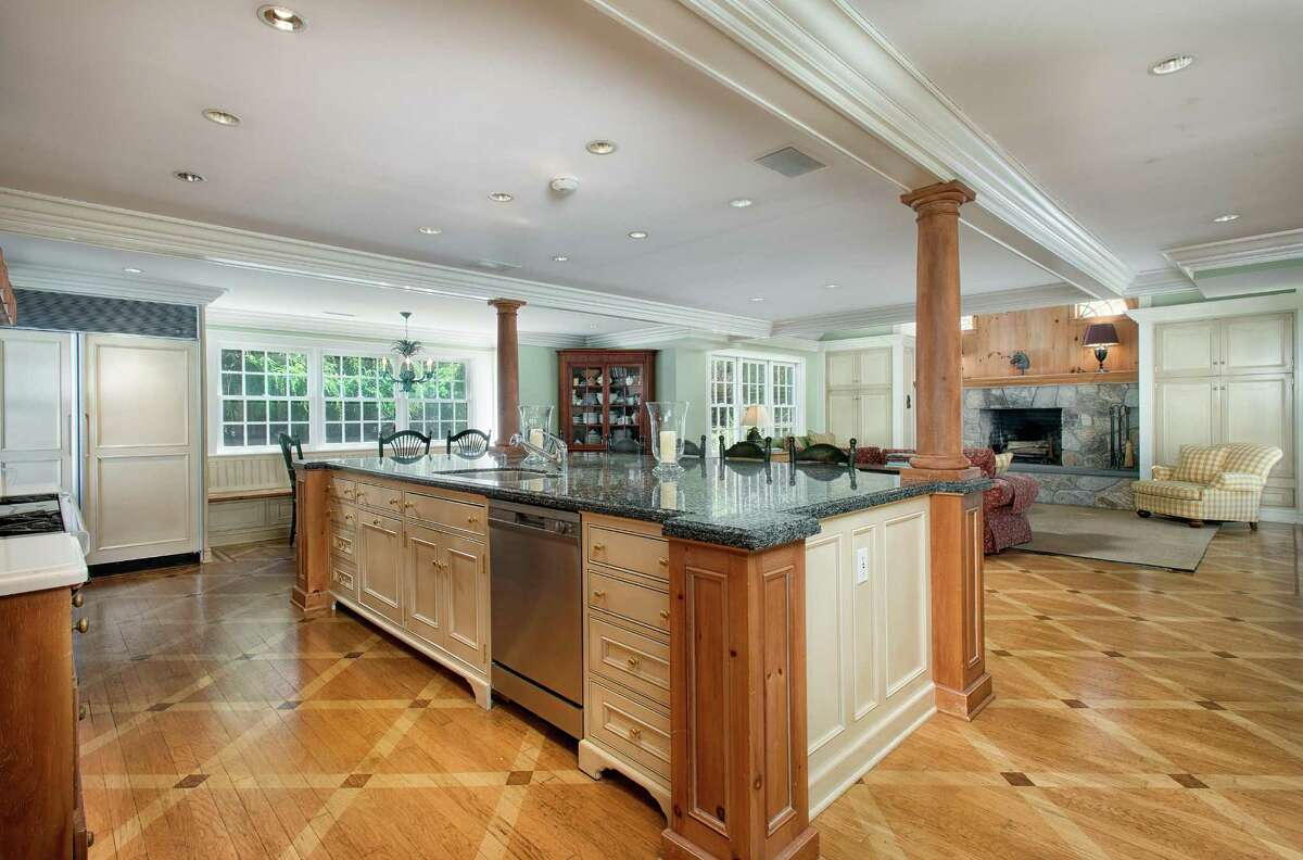 The gourmet kitchen features a large granite-topped center island with a breakfast bar, an eat-in area with a long built-in window seat, and a distinctive wood floor in an attractive pattern.