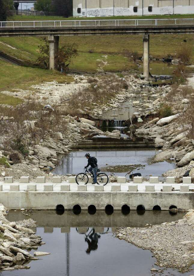 A bicyclist crosses Alazan Creek Thursday, Jan. 5, 2017  on the Apache Creek Trailway just up stream from the intersection of the two waterways. Photo: William Luther, Staff / San Antonio Express-News / © 2017 San Antonio Express-News