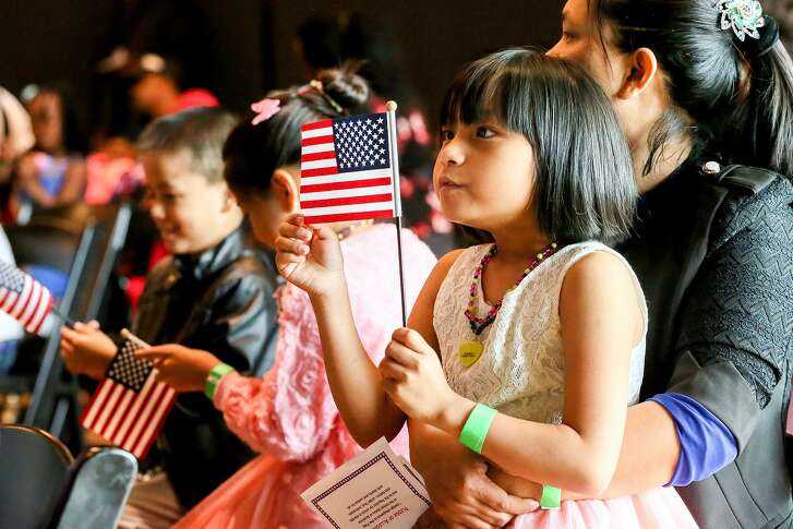 Victoria Saw, 6, looks at an American flag while sitting in her mother's lap during a Children's Citizenship Ceremony at the DoSeum, San Antonio's museum for kids, on Saturday, Jan. 14, 2017.  Fourty-two immigrant children from 21 different countries took the oath to become United States citizens at the ceremony as part of Dream Week events.  MARVIN PFEIFFER/ mpfeiffer@express-news.net