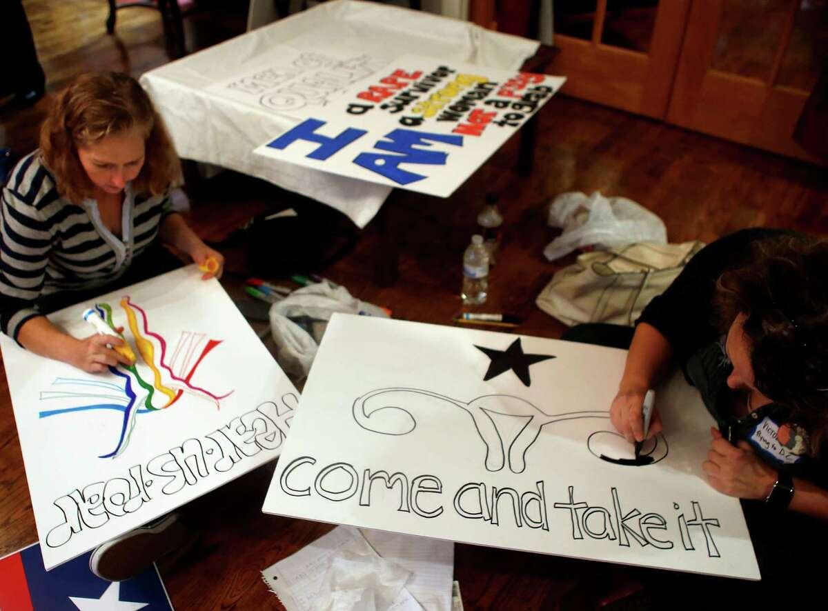 Houstonians make posters for marches planned Saturday in both Houston and Washington, D.C.