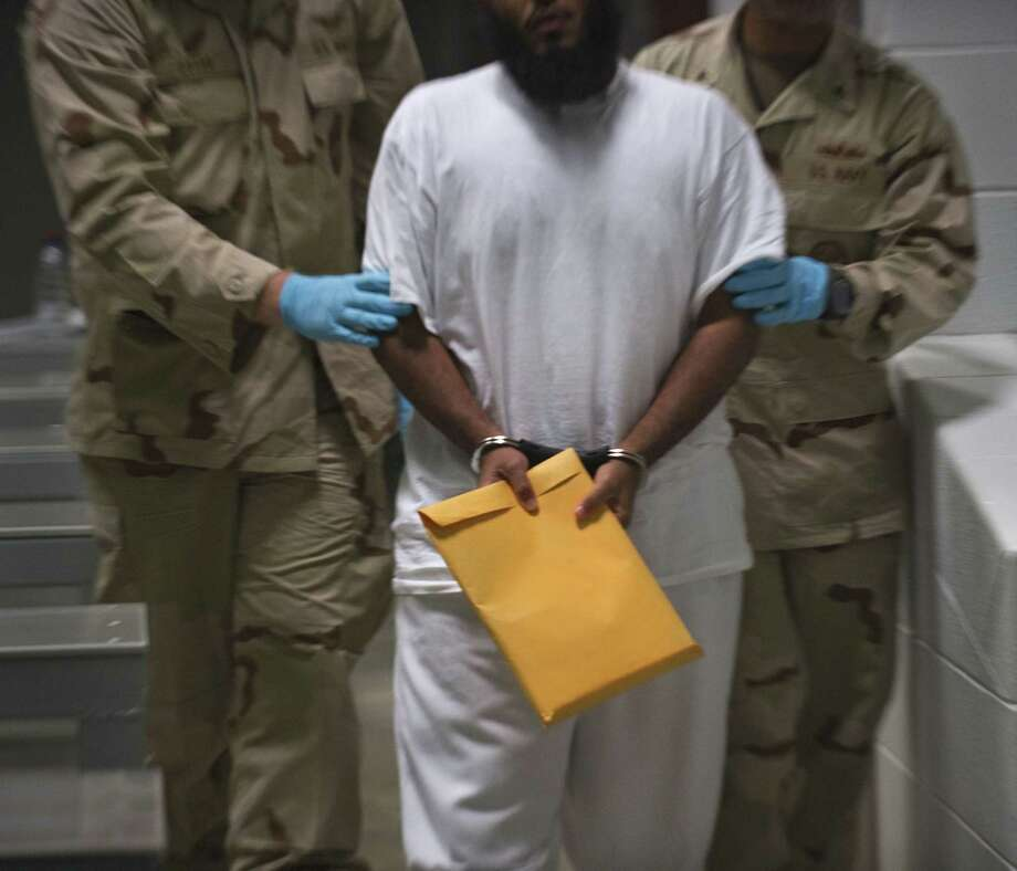 (FILES) This file photo taken on March 30, 2010 reviewed by US military officials, US military guards at Campt VI move a detainee back to his cell after he attended a lifeskills class that included resume writing at the US Detention Center in Guantanamo Bay, Cuba. Oman said it received 10 inmates from the US military prison at Guantanamo Bay on January 16, 2017, in a move to reduce their number days before US President Barack Obama leaves office. / AFP PHOTO / PAUL J. RICHARDSPAUL J. RICHARDS/AFP/Getty Images Photo: PAUL J. RICHARDS, Staff / AFP/Getty Images / AFP or licensors