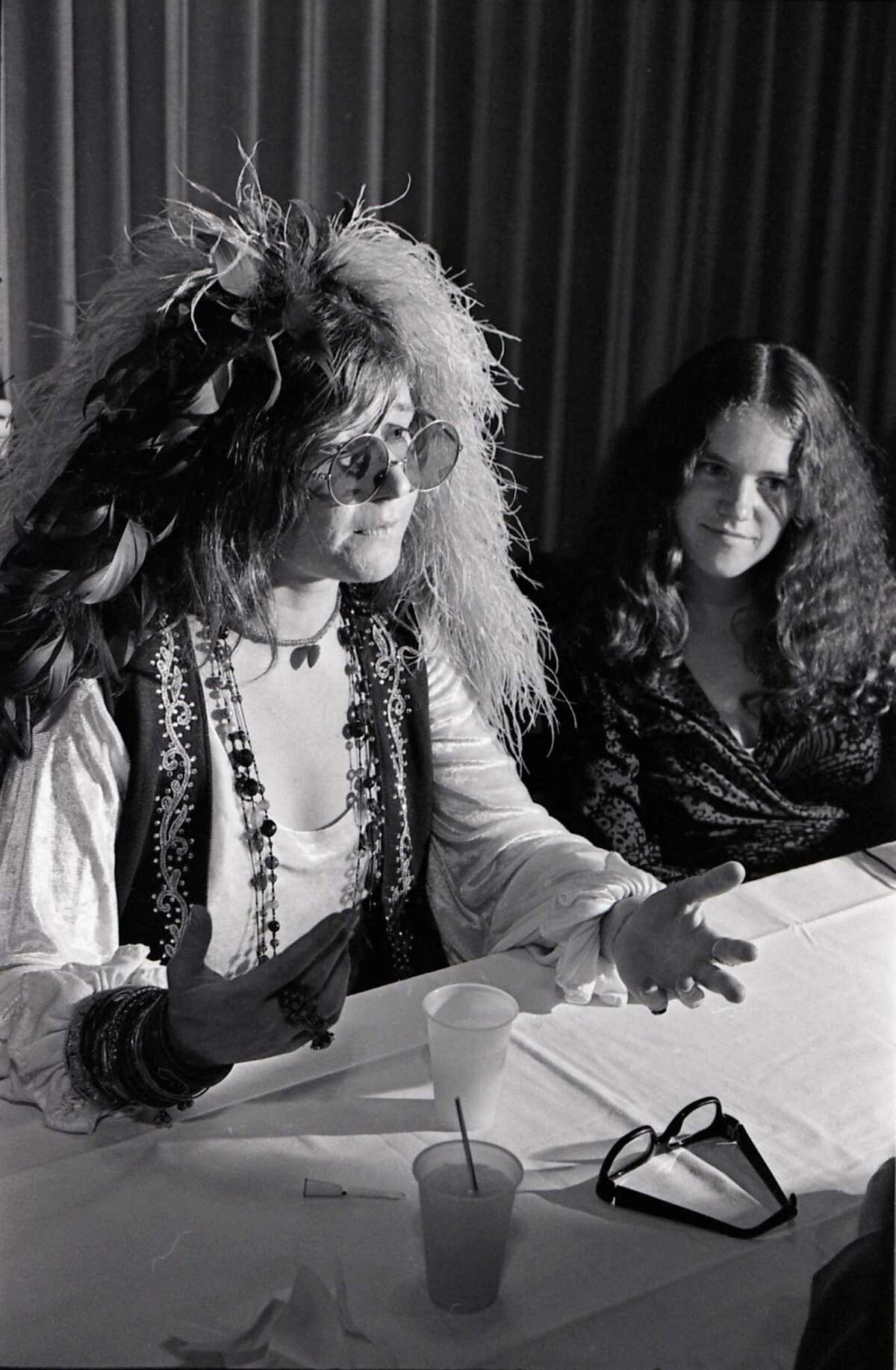 Singer Janis Joplin, left, speaks at a news conference before her high school reunion at the Goodhue Hotel.