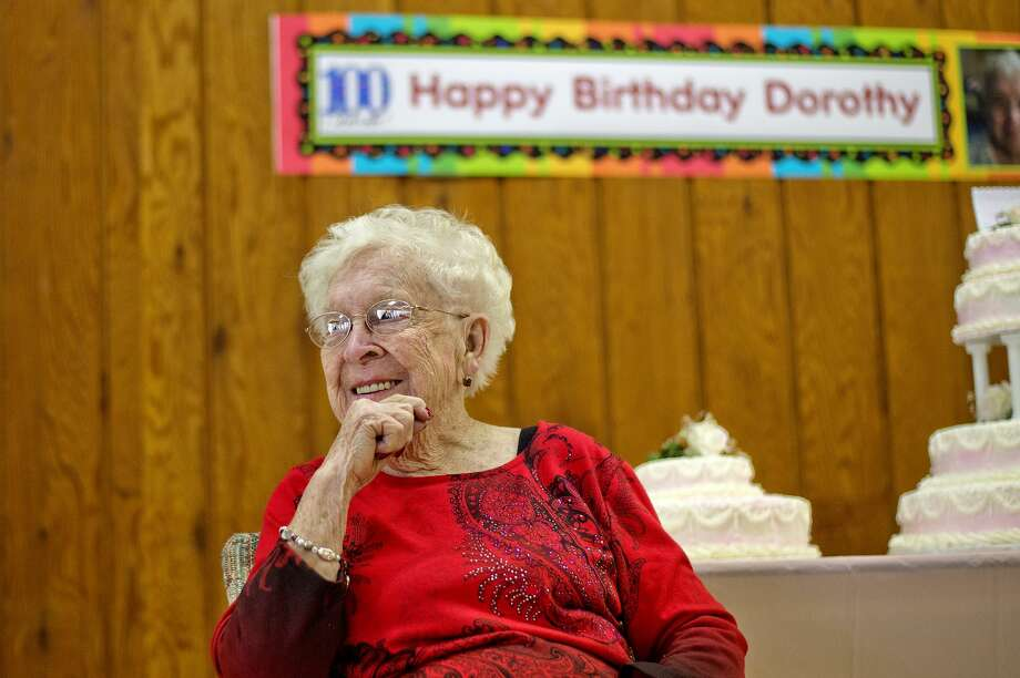 Dorothy Boman, right, listens as guests tell stories about her during her 100th birthday party on Saturday at the Swanton Memorial Center in Edenville.  Photo: Nick King/Midland Daily News