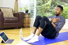 African American adult male doing a core workout using a smart tablet to guide his workout