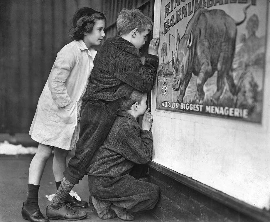 Children peer through a small opening in a door at Madison Square Garden in New York, trying to get a peak at performers for the Ringling Bros. and Barnum & Bailey Circus in 1946. The circus' owner Feld Entertainment has announced that after 146 years of performances, Ringling will soon fold its big tent forever, citing declining ticket sales, which dropped even more drastically after elephants were phased out from the shows last year. Photo: ERNIE SISTO, NYT
