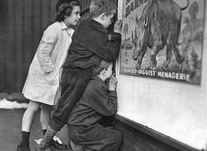 FILE -- Children peer through a small opening in a door at Madison Square Garden in New York, trying to get a peak at performers for the Ringling Bros. and Barnum & Bailey Circus, in 1946. The circus's owner Feld Entertainment has announced that after 146 years of performances, Ringling will soon fold its big tent forever, citing declining ticket sales, which dropped even more drastically after elephants were phased out from the shows last year.  (Ernie Sisto/The New York Times)