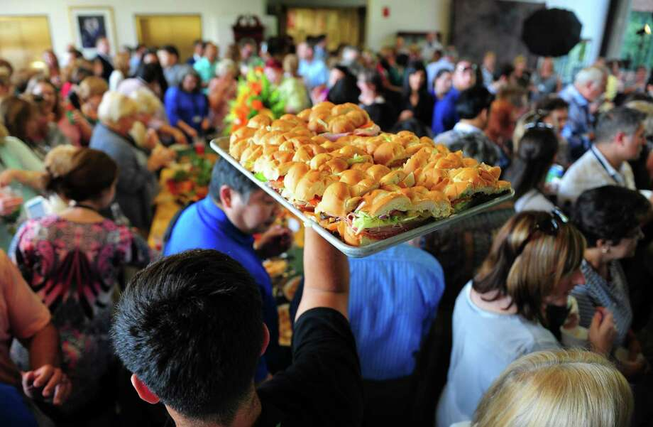 A caterer holds up a tray of Subway sandwiches for guests during the company's 50th anniversary celebration in its world headquarters in Milford in 2015. Subway said it is hiring more than 150 people in 2017. Photo: Christian Abraham / File Photo / Connecticut Post