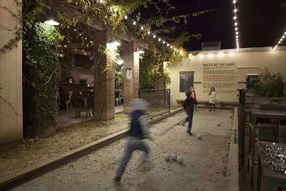 Kids play bocce ball on the outdoor patio behind Campo Fina restaurant. Photo: Peter DaSilva