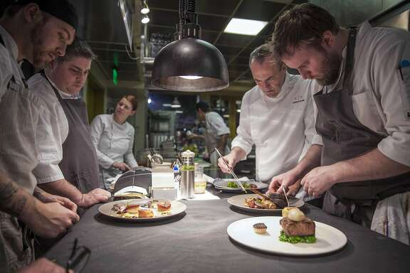 Dry Creek Kitchen executive chef Scottie Romano (left rear), Chef Charlie Palmer (right rear) line cook Michael Cochren (left front) and Sous chef Kyle Buchanan (right front) peeping plate during service, Saturday January, 07 2017 in Healdsburg, CA. (Peter DaSilva Special to the Chronicle)