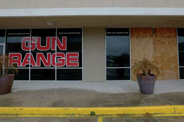 Plywood boards are installed to cover a part of the glass after an attempted burglary at Full Armor Gun Range shortly after midnight Tuesday, Jan. 17, 2017, in Houston. Two gun shop employees exchanged fire with the suspects when the suspects were trying to break in.