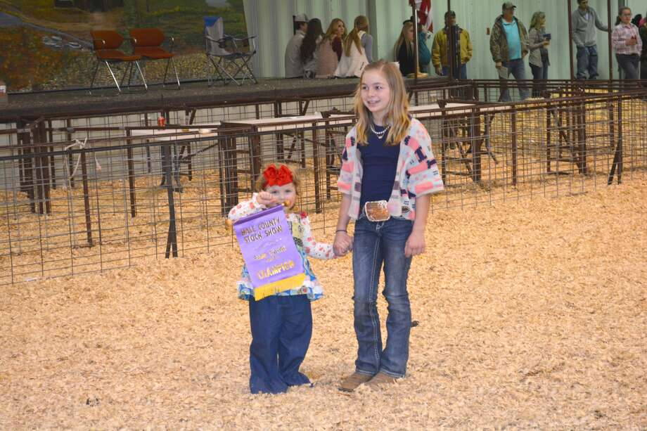 Helping draw bids for Landry Miller's Grand Champion pig at Monday's premium auction concluding the 82nd Annual Hale County Stock Show are Colter Martin (left), holding Landry's championship banner, and Landry's sister Sydney Miller. Landry, representing Abernathy 4-H, received $1,600 from Hill Veterinary Clinic in Abernathy, K&W Equipment in Hale Center and Harold and Linda Bufe of Abernathy. Sydney exhibited the Reserve Grand Champion pig.