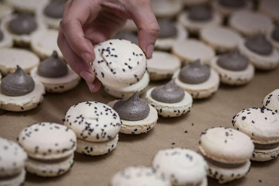 Hillary Burdock finishes up a tray of black sesame seed coconut macarons with decoration at Moustache Baked Goods. Photo: Peter DaSilva