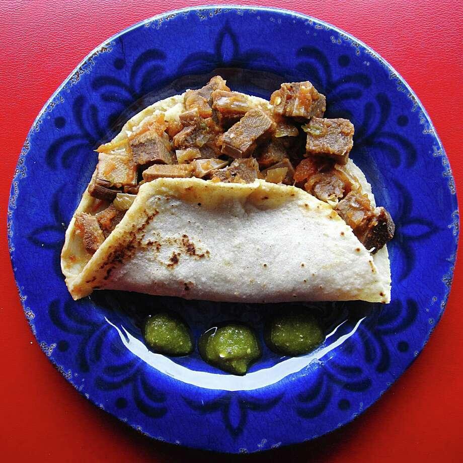 Lengua guisada taco on a handmade corn tortilla from Tia's Taco Hut on Huebner Road. Photo: Mike Sutter /San Antonio Express-News