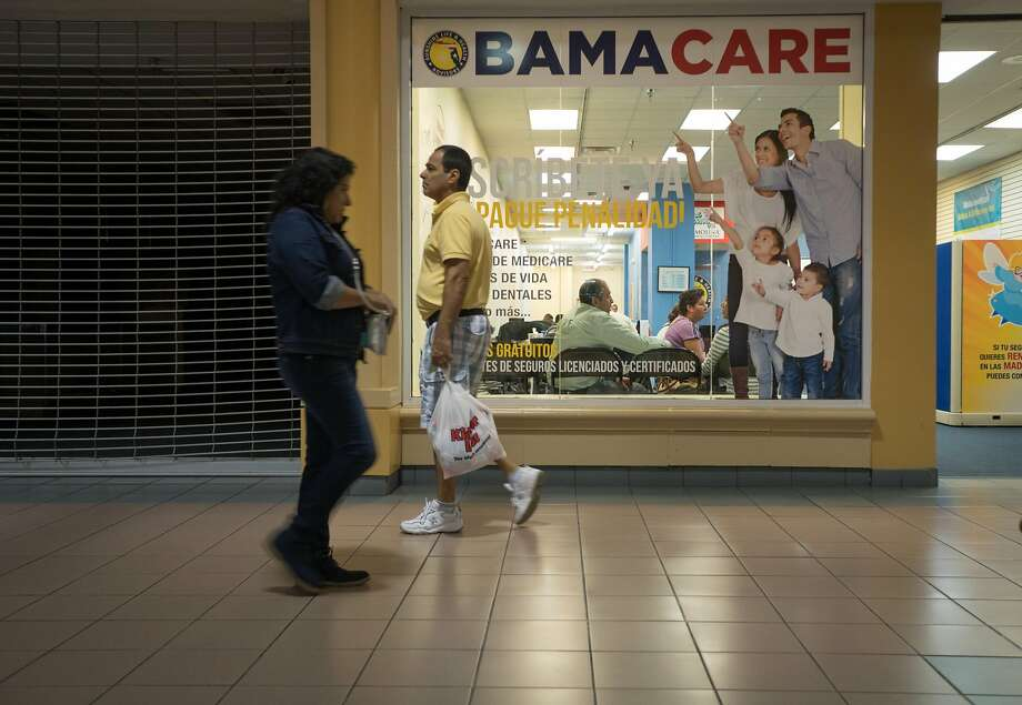 Shoppers last year walked by a health advisory agency in Miami touting the Affordable Care Act. Photo: ANGEL VALENTIN, NYT