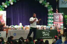 Former Texans player Wade Smith talked to kids at Browning Elementary at Tuesday's launch of the new My Home Library program.