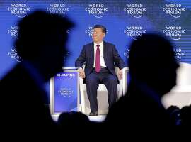 China's President Xi Jinping sits on the podium while people leave at the World Economic Forum in Davos, Switzerland, Tuesday, Jan. 17, 2017. (AP Photo/Michel Euler)