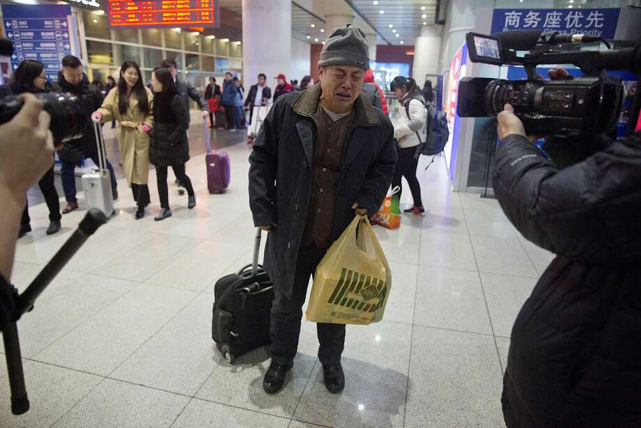 Wen Wanchang, whose son was aboard Malaysia Airlines Flight MH370, reacts to news that the search for the missing plane has been suspended as news crews film him at Beijing's train station. Photo: Ng Han Guan, Associated Press