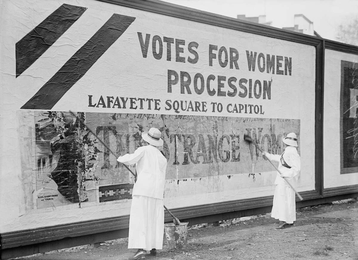 Two Women Putting Up Poster for Women's Suffrage Parade, Washington DC, USA, circa 1914. (Photo by: Universal History Archive/UIG via Getty Images)